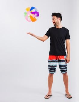 Homem com roupas de praia brincando com bola