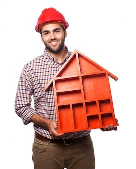 Homem com uma casa em suas mãos