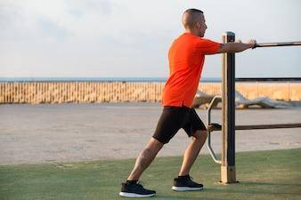 Homem confiante que se exercita no campo de jogos na manhã