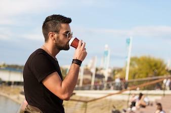 Homem considerável que bebe ao ar livre o café. Com óculos de sol, um cara com barba. Efeito Instagram.