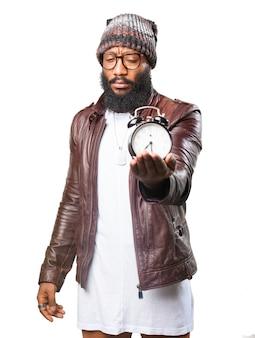 Homem de frente, segurando um relógio de alarme