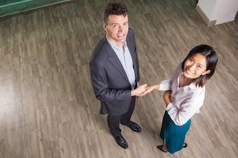 Homem de negócio feliz e mulher que agitam as mãos no salão