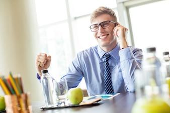Homem de negócios alegre falando no telefone na mesa