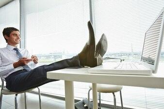 Homem de negócios com os pés sobre a mesa do computador