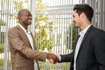 Homem de negócios feliz apertando as mãos com um colega