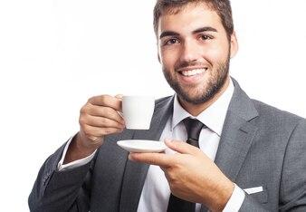 Homem de negócios feliz que levanta com um copo e um pires