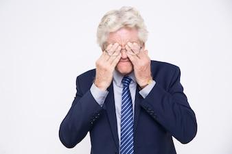 Homem de negócios forçado caucasiano sênior esfregando os olhos