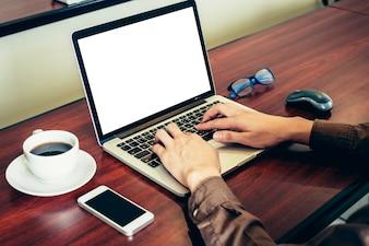 Homem de negócios que usa o laptop na mesa de madeira no escritório.