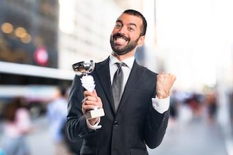 Homem de negócios segurando um troféu em fundo não focado