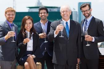 Homem de negócios sênior com mais pessoas de negócios com taças de champanhe