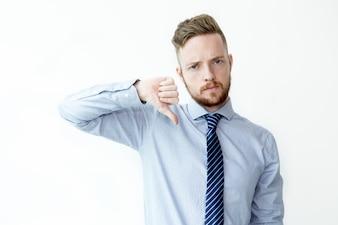 Homem de negócios sério mostrando o polegar para baixo