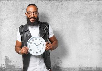 Homem de óculos segurando um relógio