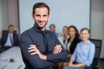 Homem de sorriso com terno sentado em uma mesa com os colegas atrás