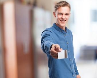 Homem de sorriso que dá um cartão de crédito