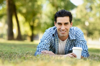 Homem de sorriso que encontra-se no gramado com um café