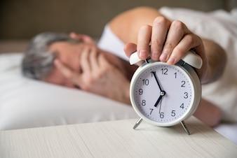 Homem deitado na cama desligando um despertador de manhã às 7 da manhã. Homem atraente dormindo em seu quarto. Homem irritado sendo despertado por um despertador em seu quarto