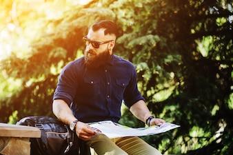 Homem distraído com um mapa no por do sol