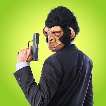 Homem do macaco com uma arma no fundo colorido