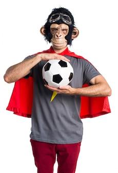Homem do macaco do super-herói segurando uma bola de futebol