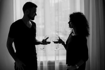 Homem e mulher clang óculos com vinho de pé diante da janela