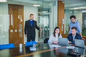 Homem entrando na sala com colegas de trabalho