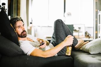 Homem farpado lounging com cerveja no ônibus