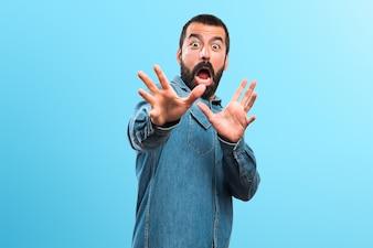 Homem fazendo gesto surpresa em fundo colorido