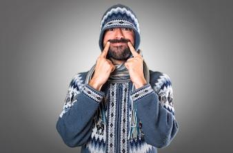 Homem feliz com roupas de inverno em fundo cinza
