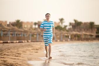 Homem feliz que funciona ao longo do seashore