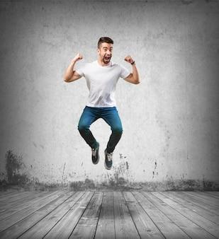 Homem feliz que salta no chão de madeira