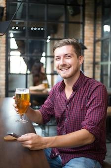 Homem feliz segurando o smartphone e copo de cerveja