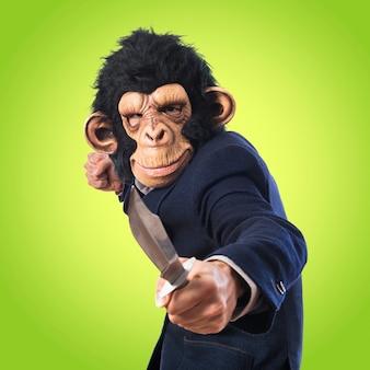 Homem macaco com faca em fundo colorido