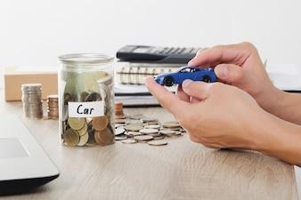 Homem mão segurando brinquedo de carro na pilha de moedas para empréstimo de seguro e conceito de carro de compra
