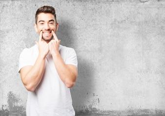 Homem marcando seu sorriso com dois dedos