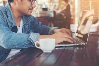 Homem moderno beber café ao usar o computador tablet no café.