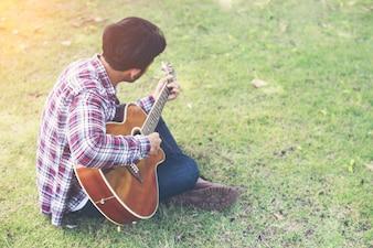 Homem moderno jovens praticada guitarra no parque, feliz e desfrutar de p