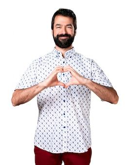 Homem moreno bonito com barba fazendo um coração com as mãos