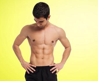 Homem muscular sem camisa com fundo amarelo