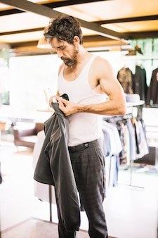 Homem na loja de roupas comprando cabides