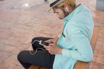 Homem novo do hipster considerável com os auscultadores brancos fora na cidade. Descontraindo.