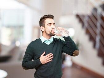 Homem novo que bebe água com uma mão no peito