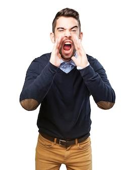 Homem novo que grita com as mãos perto da boca