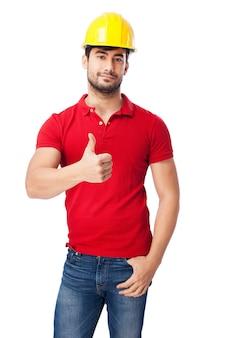 Homem novo que mostra o polegar acima no fundo branco