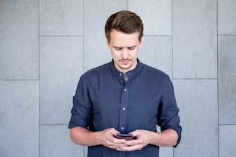 Homem novo sério que texting a mensagem no smartphone