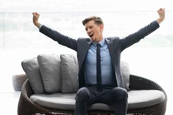 Homem novo Tired que senta no sofá e bocejando