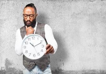 Homem pensativo com laço que olha o relógio