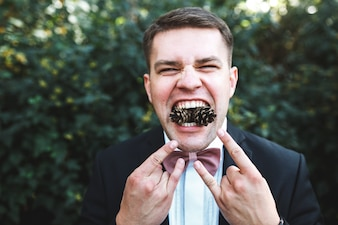 Homem posando com cones de pinheiro na boca