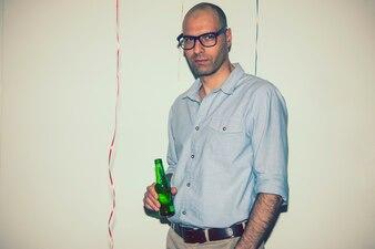 Homem posando com uma cerveja na festa