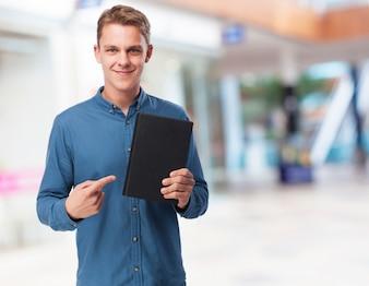 Homem que aponta em um caderno preto