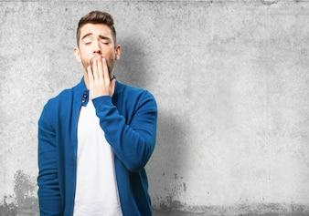 Homem que cobre sua boca ao bocejar